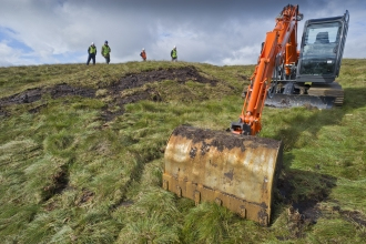 Digger and people on peatland
